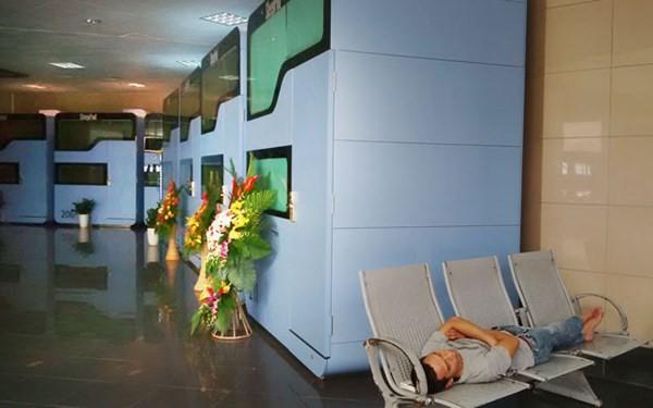 Một hành khách nằm ngủ trên hàng ghế cạnh hộp ngủ ở sân bay Nội Bài.