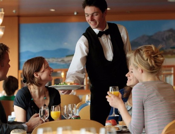 family-eating-in-the-restaurant_-waiter-serving-food-to-the-table_base1-590x442