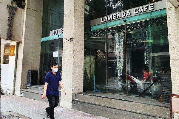 Một người đi ngang một khách sạn đang tạm ngừng hoạt động ở TPHCM. Ảnh: Đào Loan